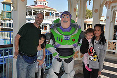 Family of four on Disneyland Vacation posing with Buzz Lightyear