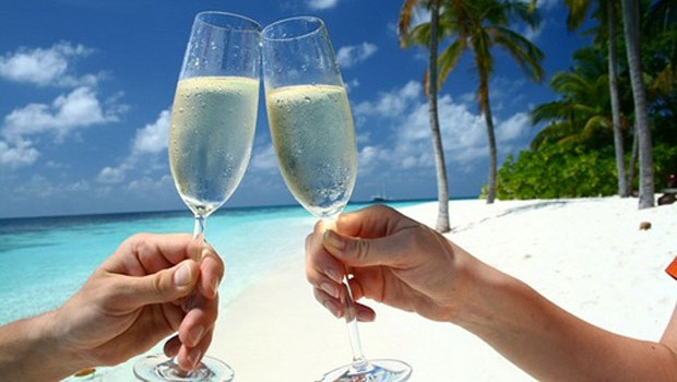 Two champagne glasses clinking on the beach