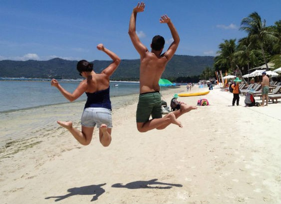 Couple jumping on a beach in Thailand