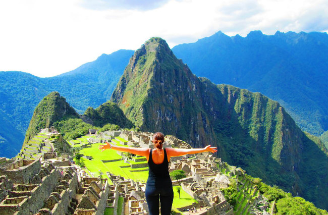 Woman with arms open in front of Machu Picchu