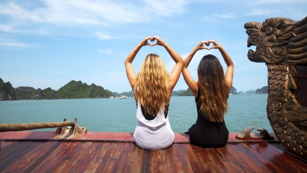 Two girls making hearts on the water in Thailand