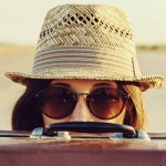 Hipster woman in hat and glasses looks out from vintage suitcase