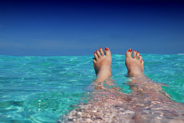 Feet up in the ocean in the Maldives