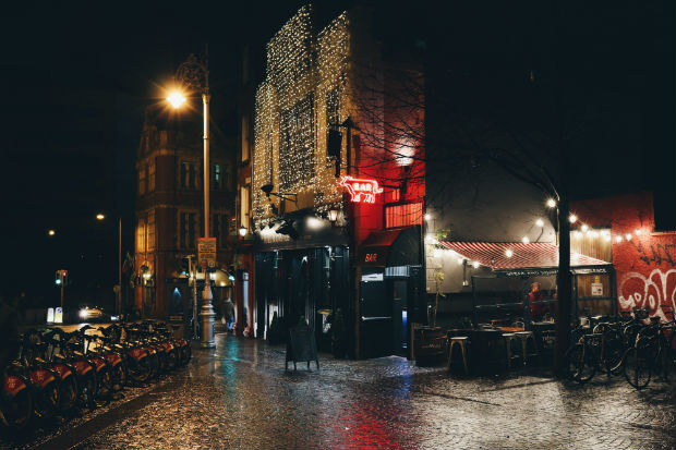 historic dublin at night cobblestone streets wet with rain and reflecting bar lights