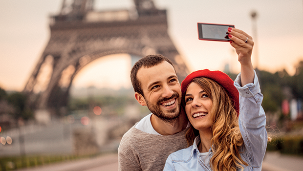 couple taking a selfie by the eiffel tower in paris france