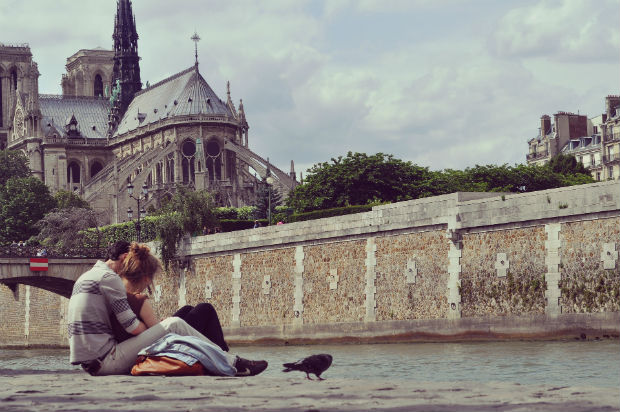 couple sitting by the river in paris