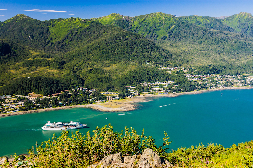 A luxury cruise ship sails along a narrow straight to reach Juneau, Alaska. on an August morning.