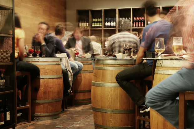 patrons drinking wine on barrels in spain
