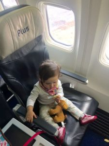 baby on plane snacks toy puppy