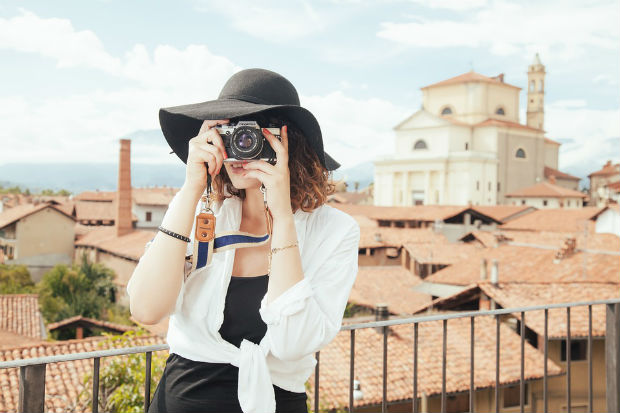 travel photography woman taking a photo travelling Olympus camera bag essential gear