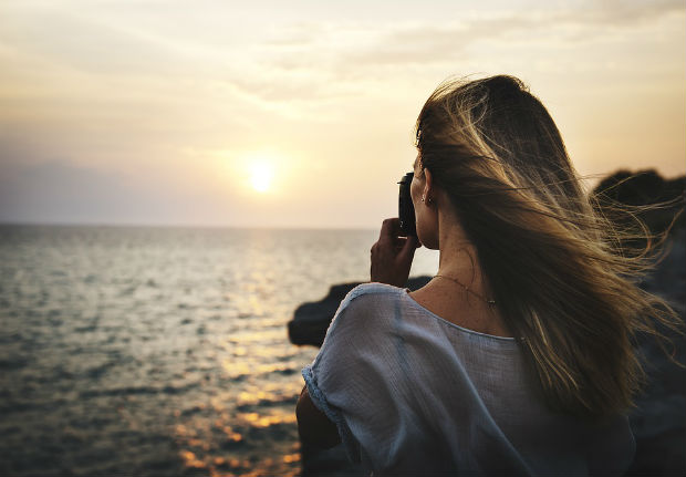 travel photography woman taking photo of sunset
