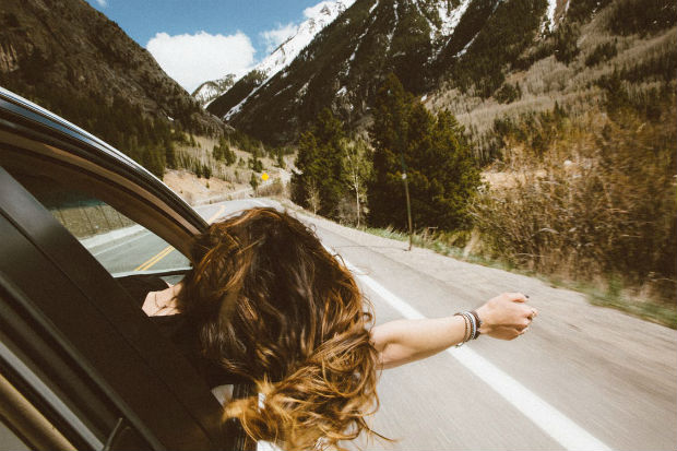 carefree girl on road trip wind in hair drive bc alberta rockies rocky mountains