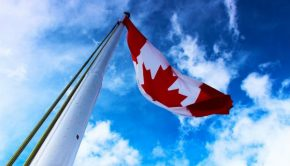 large canada flag slying on tall flagpole blue sky proud canadian