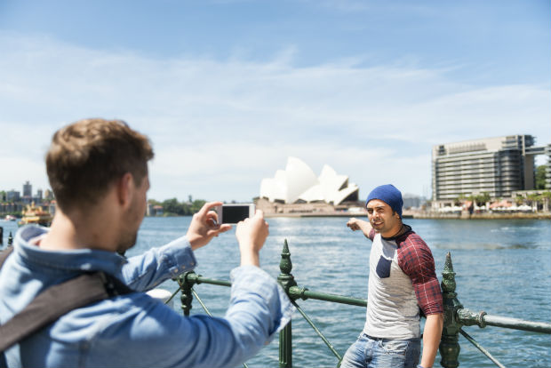 man taking photos across the sydney opera house