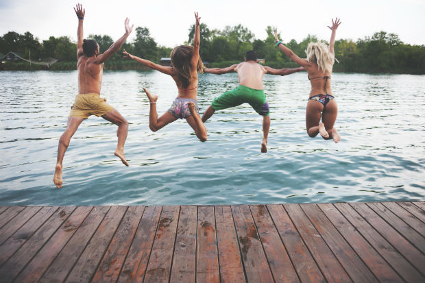 friends jumping into a lake