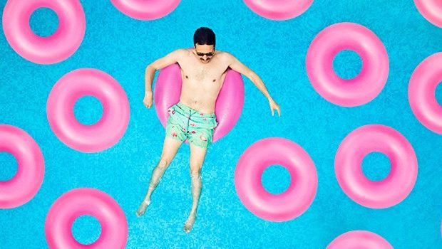 man in floating donut in a pool in the summer