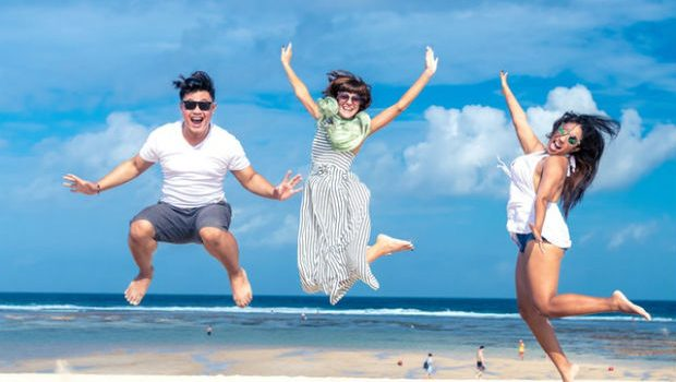 westjet vacations flight centre travel contest three happy people jumping for joy on beautiful white sand beach in sunshine