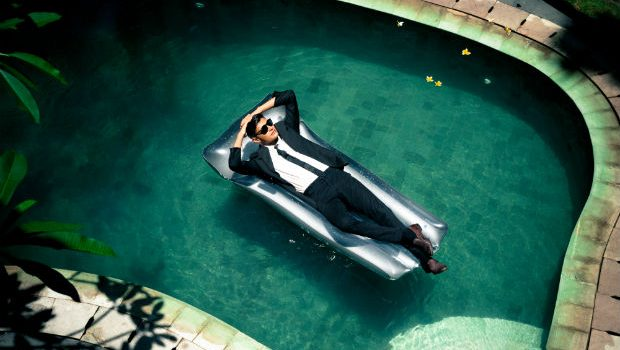 business travel man in suit on floatie in pool
