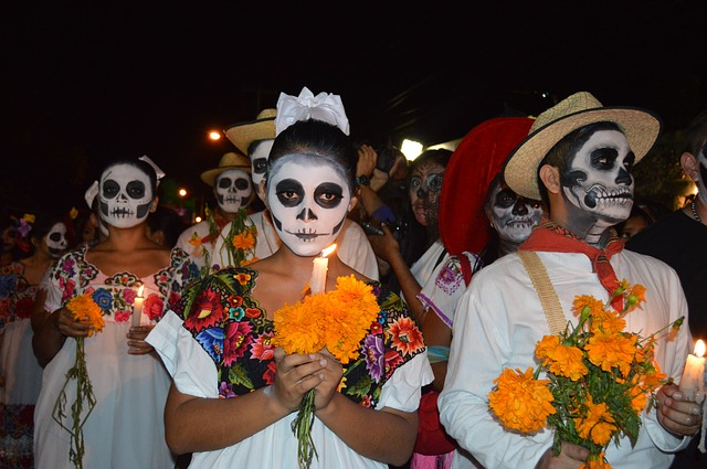 girl in skull makeup carrying marigolds during dia de los muertos