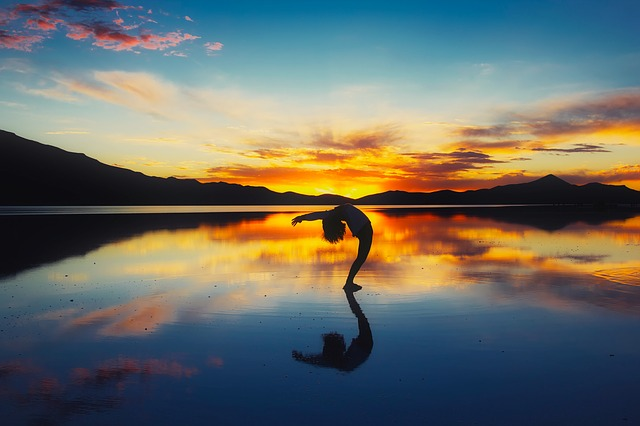 girl doing yoga on the beach at sunset