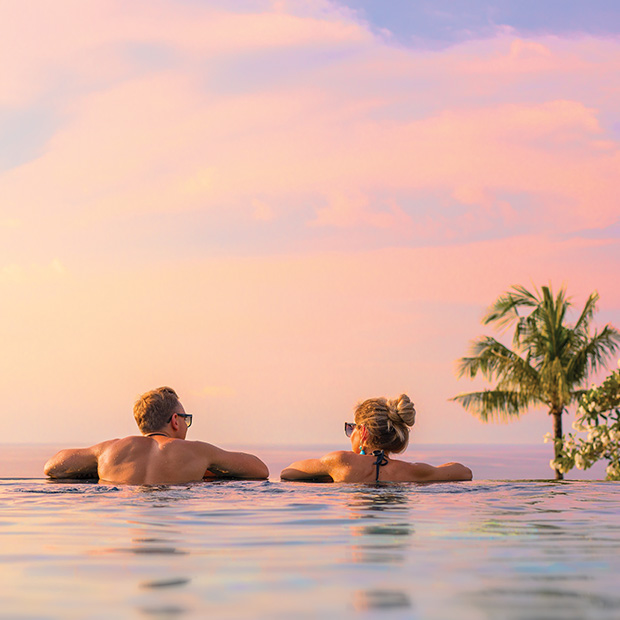 couple-relax-in-infinity-pool-beach-vacation