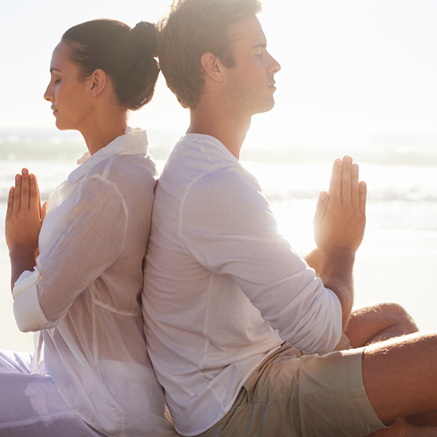 couple-meditating-on-beach