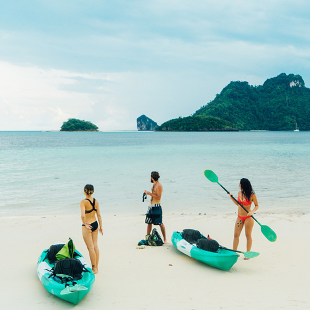 wellness travel kayak women on beach