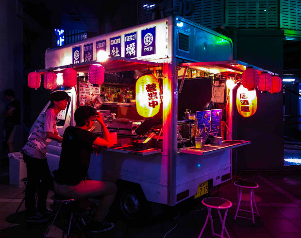 summer night in japan, people eating street food at night from a vendor