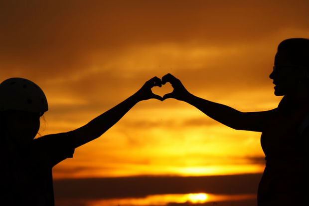 silhouette of mom and child's hands creating a heart with the sunset over the beach in the background