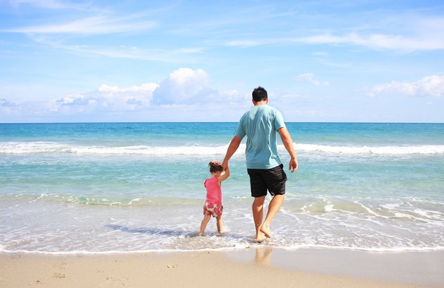 dad and small daughter holding hands stepping into the ocean on the beach