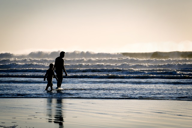 single parent and child on beach with rolling waves that look like crashing horizontal lines