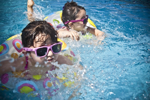 two girls with pink sunglasses and water wings in swimming pool