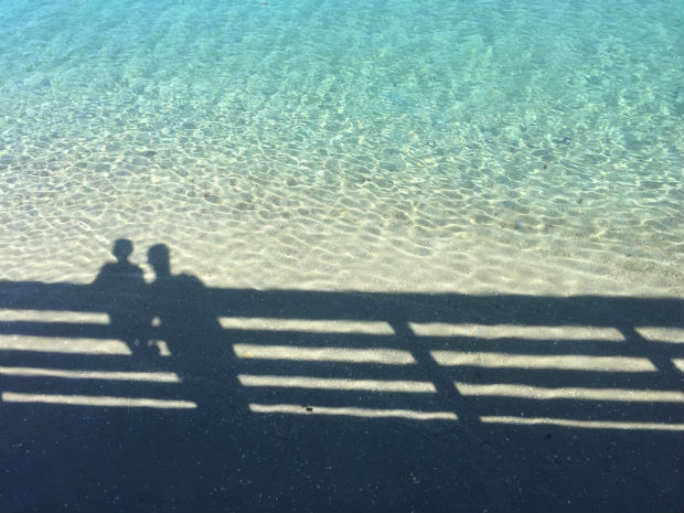 shadows of a parent and child reflected on crystal clear ocean on the sand and shallow turquoise water