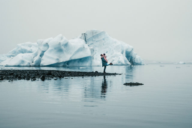 couple standing on a lake by a glacier in iceland