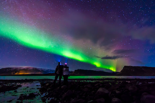 man and woman standing underneath the northern lights