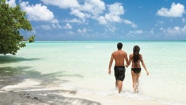 sexy man and woman walking holding hands walking through clear turquoise water and white sand on a tropical honeymoon