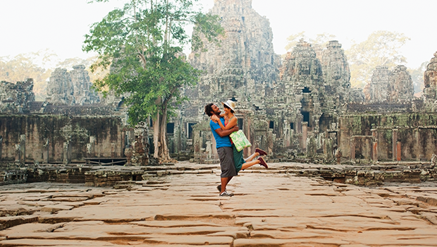 couple standing in front of angkor wat cambodia lifing her in the air