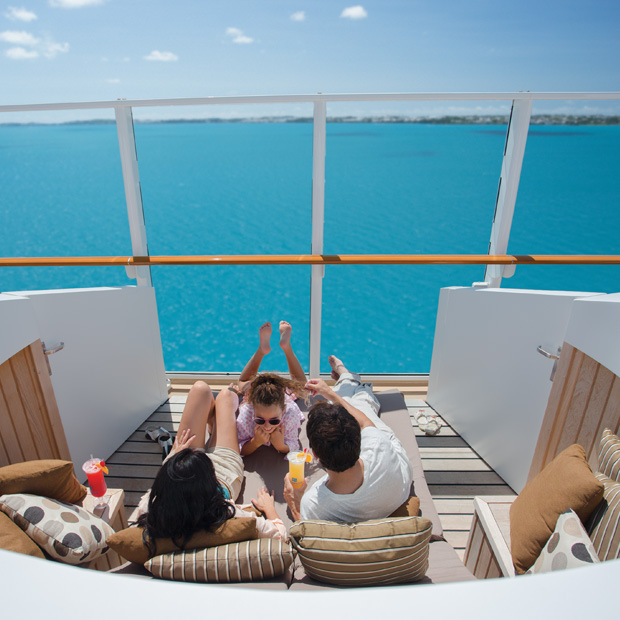 norwegian-cruise-line-beautiful-outdoor-balcony-facing-the-ocean-with safety-windows-family-enjoying-time-together