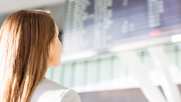 basic-economy-fares-woman-looking-at-airport-ticker