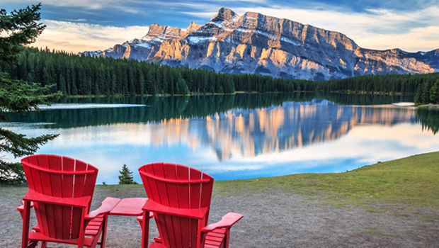 red muskoka chairs in front of mountains in canada