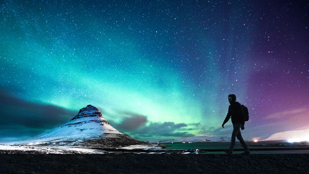man in front of northern lights in iceland