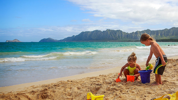 family vacation destinations in hawaii small children playing on beach in sand