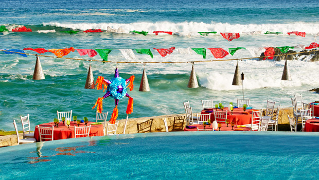 mexico family vacation destinations brightly coloured dining tables on the beach