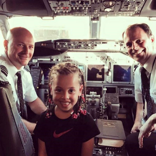 smiling child with airline captains in cocktpit travel with kids
