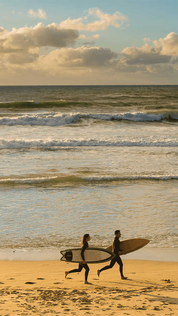 Best beaches in California - Photo of a couple running with surf boards