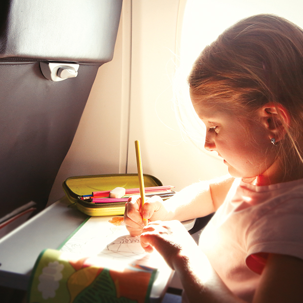 child colouring on an airplane