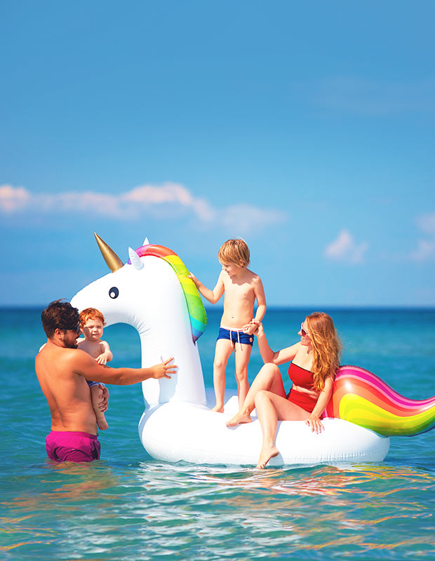 family on a unicorn floatie at the beach