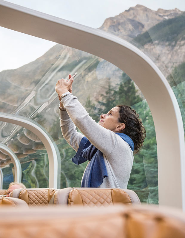 woman-takes-photos-on-her-phone-through-the-glass-dome-window-of-the-rocky-mountaineer-luxury-train