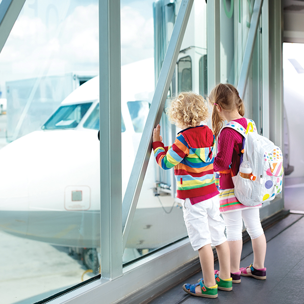 children at an airport looking at an airplane