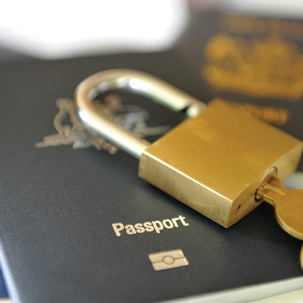 passport with a lock and key sitting on top